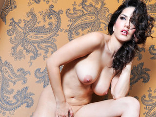 Wearing a red dress next to a red lamp, Sunny Leone strips!